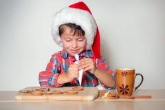 Petit garçon mignon décorant les biscuits de pain d'épice Photo stock