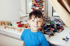 Petit garçon mignon d'élève du cours préparatoire jouant avec le smil heureux de jouets à la maison Images libres de droits