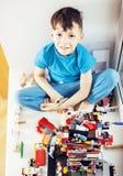 Petit garçon mignon d'élève du cours préparatoire jouant avec le sourire heureux de jouets à la maison, concept d'enfants de mode Images libres de droits