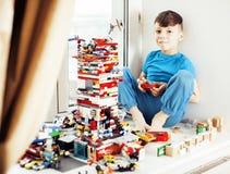 Petit garçon mignon d'élève du cours préparatoire jouant le sourire heureux de jouets à la maison, Images libres de droits