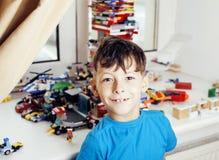 Petit garçon mignon d'élève du cours préparatoire jouant le sourire heureux de jouets à la maison, Image libre de droits
