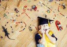 Petit garçon mignon d'élève du cours préparatoire parmi l'éducation de lego de jouets à la maison dans la pose de sourire de chap Photographie stock libre de droits