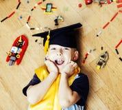 Petit garçon mignon d'élève du cours préparatoire parmi le lego de jouets à la maison dans le chapeau licencié, concept éducatif  Photos stock