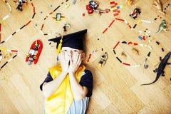 Petit garçon mignon d'élève du cours préparatoire parmi le lego de jouets à la maison dans le diplômé Images stock
