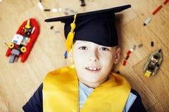 Petit garçon mignon d'élève du cours préparatoire parmi le lego de jouets à la maison dans le diplômé Images libres de droits
