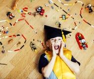 Petit garçon mignon d'élève du cours préparatoire parmi le lego de jouets à la maison dans le diplômé Photo stock