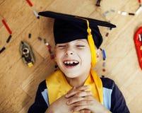 Petit garçon mignon d'élève du cours préparatoire parmi le lego de jouets à la maison dans le diplômé Photos stock