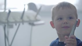 Petit garçon mignon dans le bureau de dentiste jouant tenant les outils médicaux Docteur de visite d'enfant insouciant Demande de clips vidéos