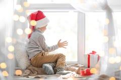 Petit garçon mignon dans le chapeau de Santa se reposant sur le rebord de fenêtre à la maison Images stock