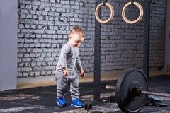Petit garçon mignon dans le sportwera gris tenant le barbell proche contre le mur de briques dans le gymnase convenable de croix Photos stock