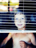 Petit garçon mignon dans toute la fenêtre faisant les visages drôles, maison seul l Photographie stock libre de droits
