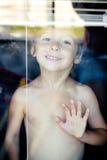 Petit garçon mignon dans toute la fenêtre faisant les visages drôles, seul concept de mode de vie de maison Image libre de droits
