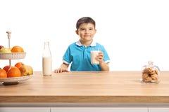 Petit garçon mignon dans un T-shirt bleu tenant un verre de lait derrière un compteur en bois photo stock
