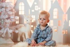 Petit garçon mignon de cheveux blonds dans les vêtements de nuit près des maisons de papier de jouet de Noël Photo libre de droits