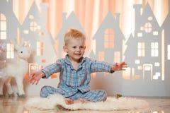 Petit garçon mignon de cheveux blonds dans les vêtements de nuit près des maisons de papier de jouet de Noël Photographie stock