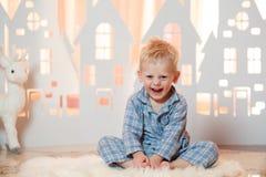 Petit garçon mignon de cheveux blonds dans les vêtements de nuit près des maisons de papier de jouet de Noël Images stock