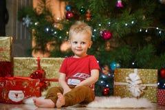 Petit garçon mignon de cheveux blonds près de la cheminée et des cadeaux sous l'arbre de Noël Images libres de droits