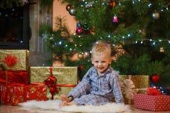 Petit garçon mignon de cheveux blonds près de la cheminée et des cadeaux sous l'arbre de Noël Photographie stock libre de droits