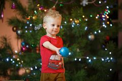 Petit garçon mignon de cheveux blonds près de la cheminée et des cadeaux sous l'arbre de Noël Photo libre de droits