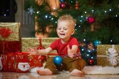 Petit garçon mignon de cheveux blonds près de la cheminée et des cadeaux sous l'arbre de Noël Photographie stock