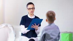 Petit garçon mignon de sourire de belle jeune d'enfant féminin consultation de psychologue à la session de thérapie banque de vidéos