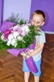 Petit garçon mignon donnant des fleurs Images stock