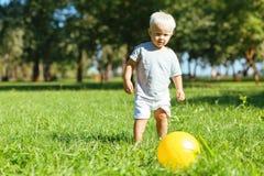Petit garçon mignon donnant un coup de pied une boule dehors images stock