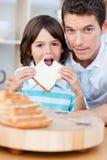 Petit garçon mignon et son père mangeant du pain photo stock