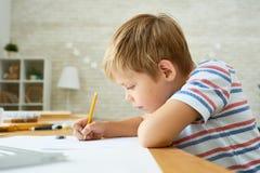 Petit garçon mignon faisant le travail Images stock