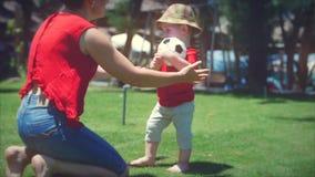 Petit garçon mignon jouant avec du ballon de football fonctionnant à sa mère dans une étreinte Longueur courante clips vidéos