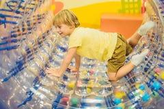 Petit garçon mignon, jouant dans Zorb un anneau en plastique de cylindre de roulement avec un trou au milieu, intdoor images stock