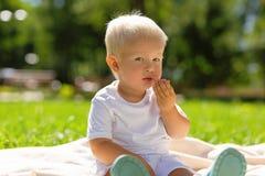 Petit garçon mignon mangeant des bonbons en parc images stock