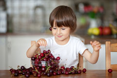 Petit garçon mignon, mangeant des cerises à la maison dans la cuisine, faisant Photographie stock
