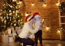 Petit garçon mignon portant le chapeau de Santa et son respect de mère ou de grand-mère un cadeau de Noël Portrait de famille heu photos libres de droits