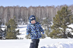 Petit garçon mignon portant les vêtements chauds jouant sur la forêt d'hiver dessus Images stock