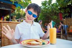 Petit garçon mignon prenant le déjeuner dans le restaurant Photo libre de droits