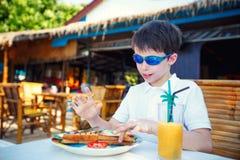 Petit garçon mignon prenant le déjeuner dans le restaurant Images stock