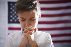 Petit garçon mignon priant sur le drapeau américain Photo stock