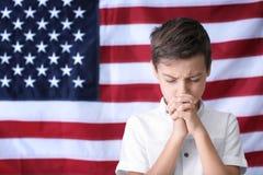 Petit garçon mignon priant sur le drapeau américain Photographie stock libre de droits