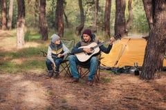 petit garçon mignon regardant le père jouant la guitare image stock