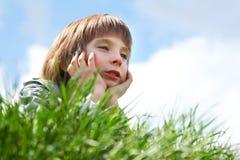 Petit garçon mignon s'étendant sur l'herbe verte au-dessus du natur de ressort de ciel bleu Images libres de droits