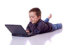 Garçon mignon avec un ordinateur portable Photographie stock libre de droits