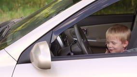 Petit garçon mignon s'asseyant derrière la roue des voitures et jouant avec le téléphone banque de vidéos