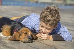 Petit garçon mignon se trouvant par la rivière avec son chiot Photographie stock