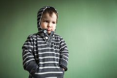 Petit garçon mignon sombre tenant des mains dans des poches images stock