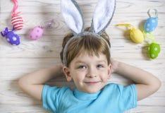 Petit garçon mignon tenant un nid avec les oeufs de pâques colorés à la maison le jour de Pâques Célébration de Pâques au ressort Images stock