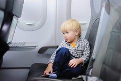 Petit garçon mignon voyageant en un avion Image stock