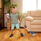 Petit garçon nettoyant l'appartement, lavant le plancher Images stock