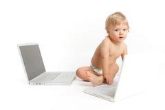 Petit garçon observé bleu travaillant sur des ordinateurs portatifs Image stock