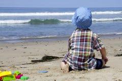 Petit garçon observant les vagues Image libre de droits